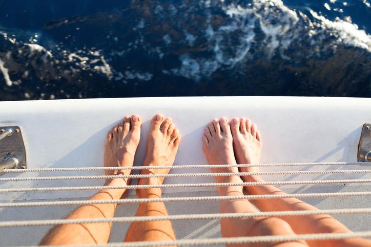 Closeup of couples feet on a yacht.