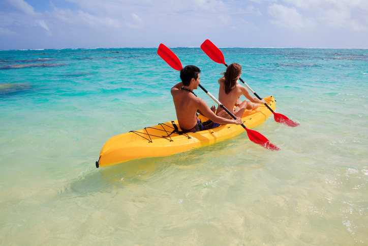 young couple kayaking in hawaii paddling out to sea