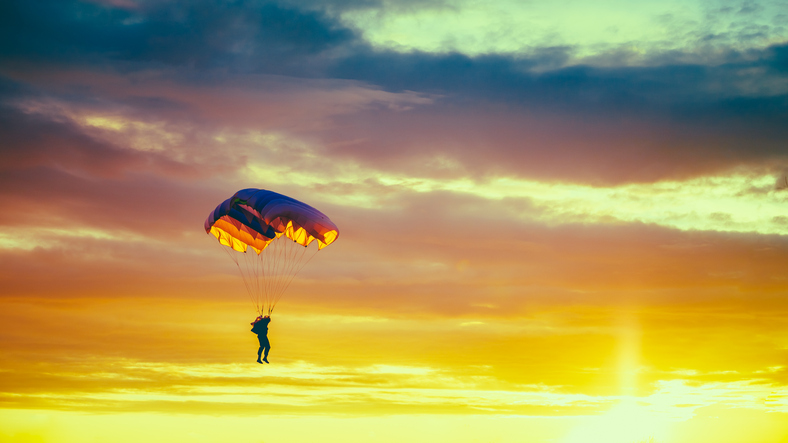 Skydiver On Colorful Parachute In Sunny Sunset Sky. Active Hobbies