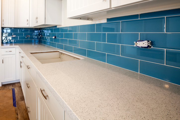 A detailed view of new construction of a kitchen counter with glass tile backsplash.